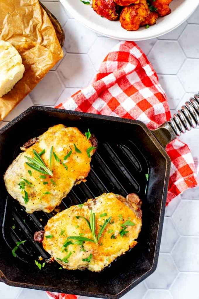 Overhead photo of a cast iron grill pan with two Parmesan Crusted Steaks sitting on a red and white napkin.