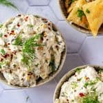 Overhead square image of dill pickle dip in two small bowls garnished with dill.