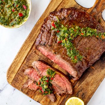 Square overhead photo of keto flank steak with three thin slices cut from it on a wooden cutting board garnished with chimichurri.