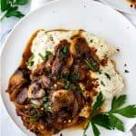 Overhead square photo of keto salisbury steak on mashed cauliflower on a white plate garnished with parsley.