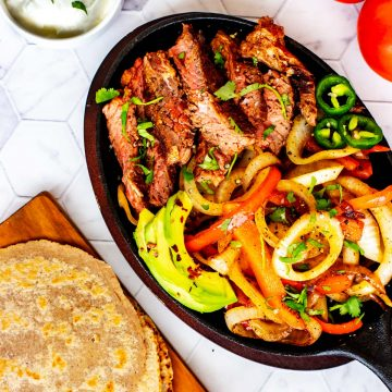 Square overhead photo of a skillet of keto steak fajitas with tortillas sitting next to it.