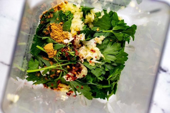 Photo of parsley, cilantro, vinegar, garlic, salt, cumin, and crushed red pepper in a blender.