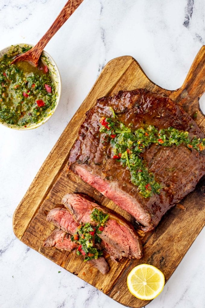 Overhead photo of keto flank steak with three thin slices cut from it on a wooden cutting board garnished with chimichurri.