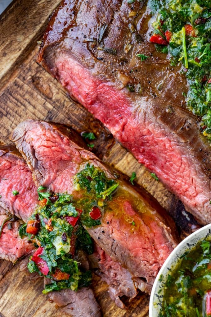 Close up photo of sliced flank steak with a whole flank steak beside it.