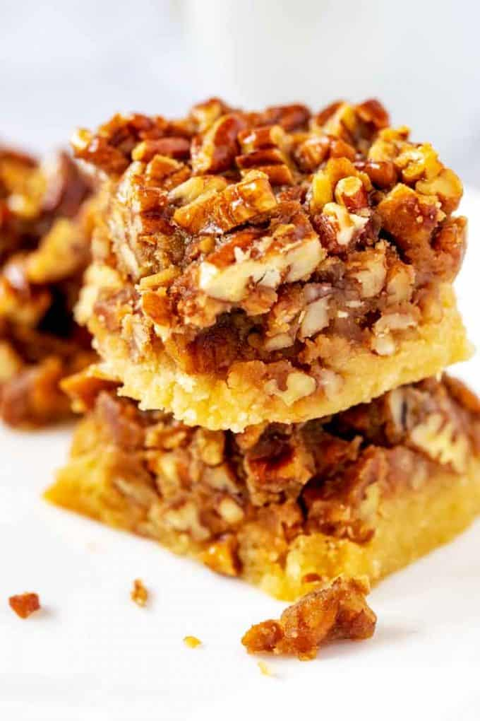 Close up photo of two keto pecan bars stacked on top of each other against a white background.