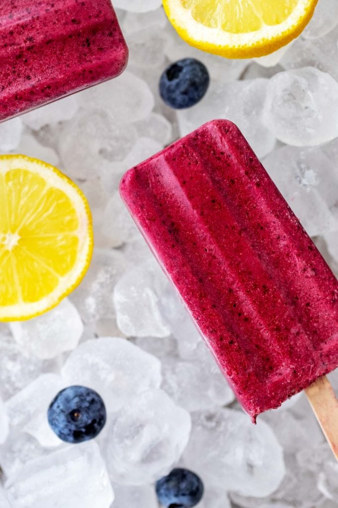 Overhead photo of one full and one partial Keto Popsicle on a bed of ice surrounded by lemon slices and fresh blueberries.