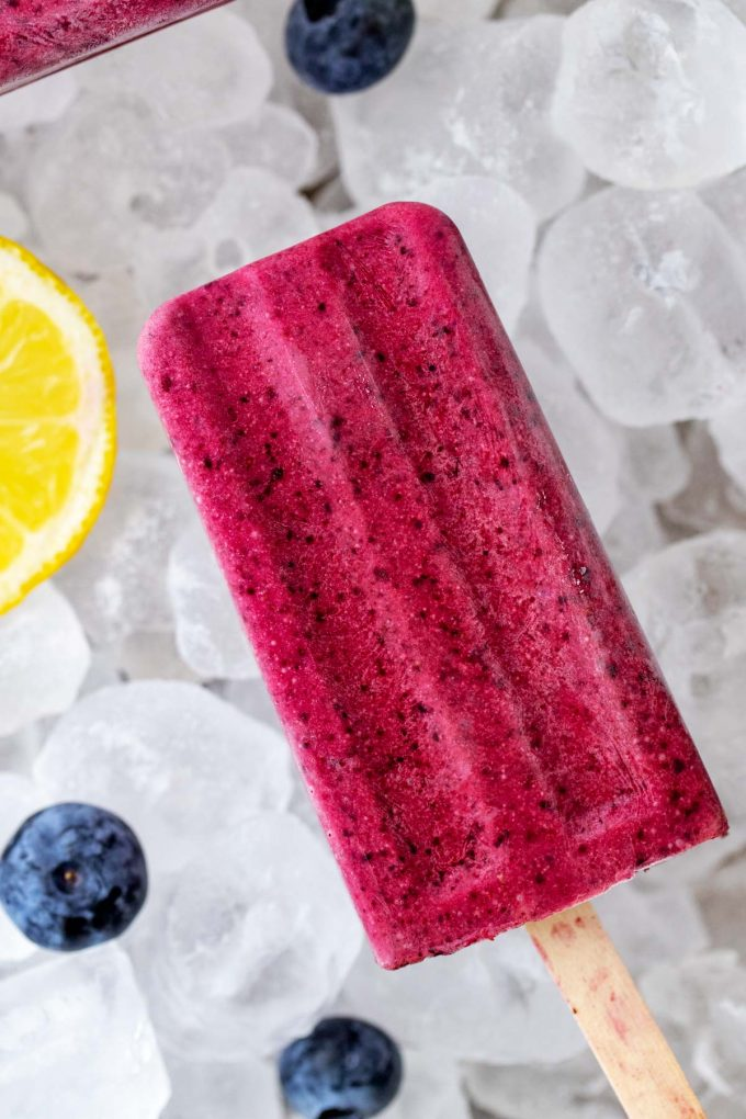 Close up overhead photo of a blueberry Keto ice Pop on a bed of ice with fresh blueberries and lemon slices surrounding it.
