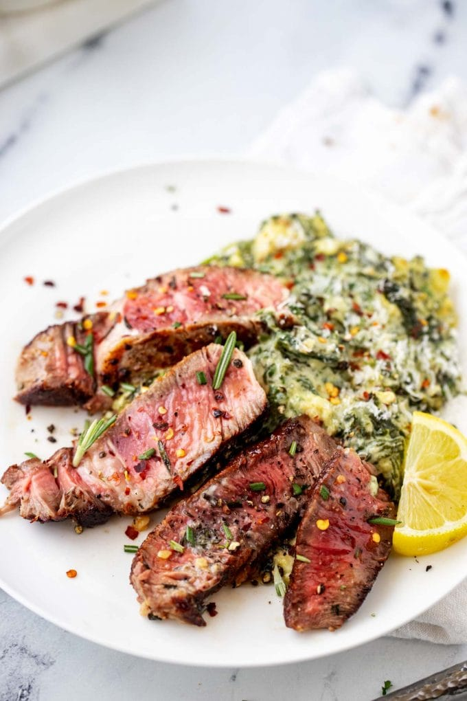 Sliced seared rib eye on a white plate with creamed spinach.