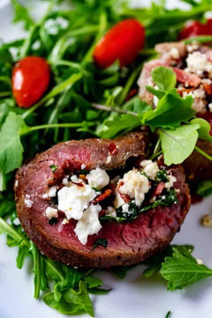 Close up photo of stuffed flank steak on a bead of greens.