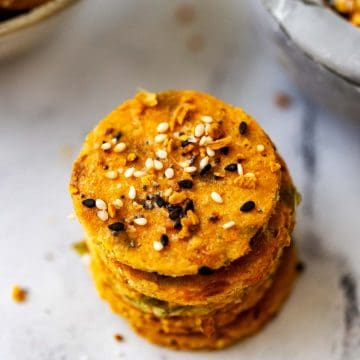 Square photo of a stack of keto crackers with a bowl of everything seasoning next to it.