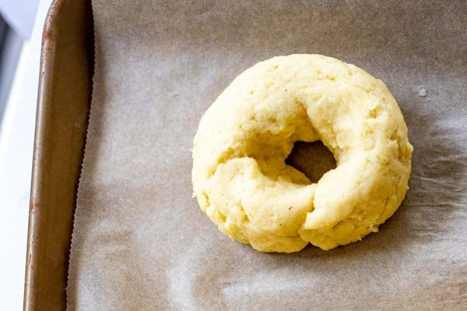 Fathead bagel that has been formed on a sheet of parchment paper.