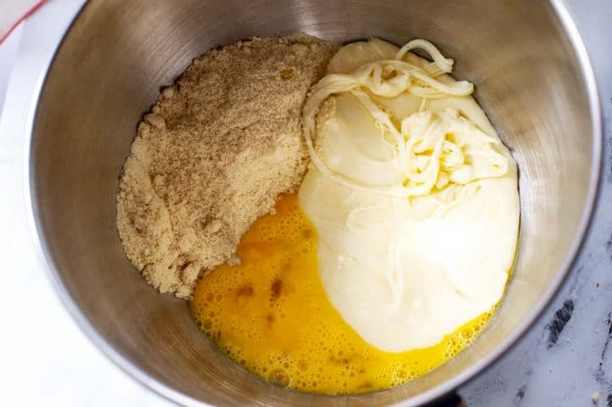 Melted cheese, almond flour, oat fiber, and egg in the bowl of a stand mixer.