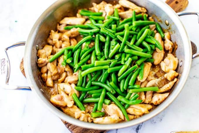 Overhead photo of chicken and green beans in a large skillet.