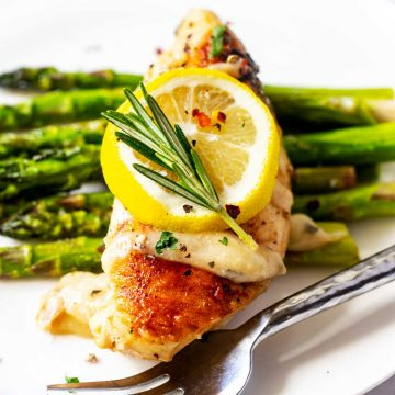 Square close up photo of a white plate with Instant Pot Rosemary Chicken sitting on top of asparagus garnished with lemon and rosemary.