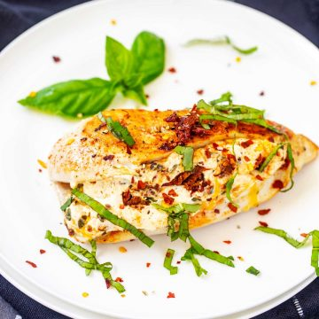 Square photo of a white plate with Keto Cream Cheese Chicken garnished with basil.