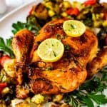 Close up square photo of keto roasted chicken surrounded by parsley and roasted vegetables.