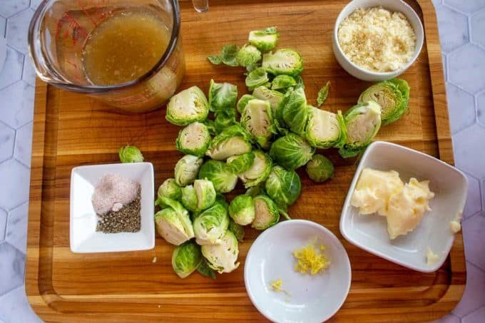 Photo of broth, Brussels Sprouts, salt, pepper, lemon zest, butter and parmesan cheese on a cutting board.