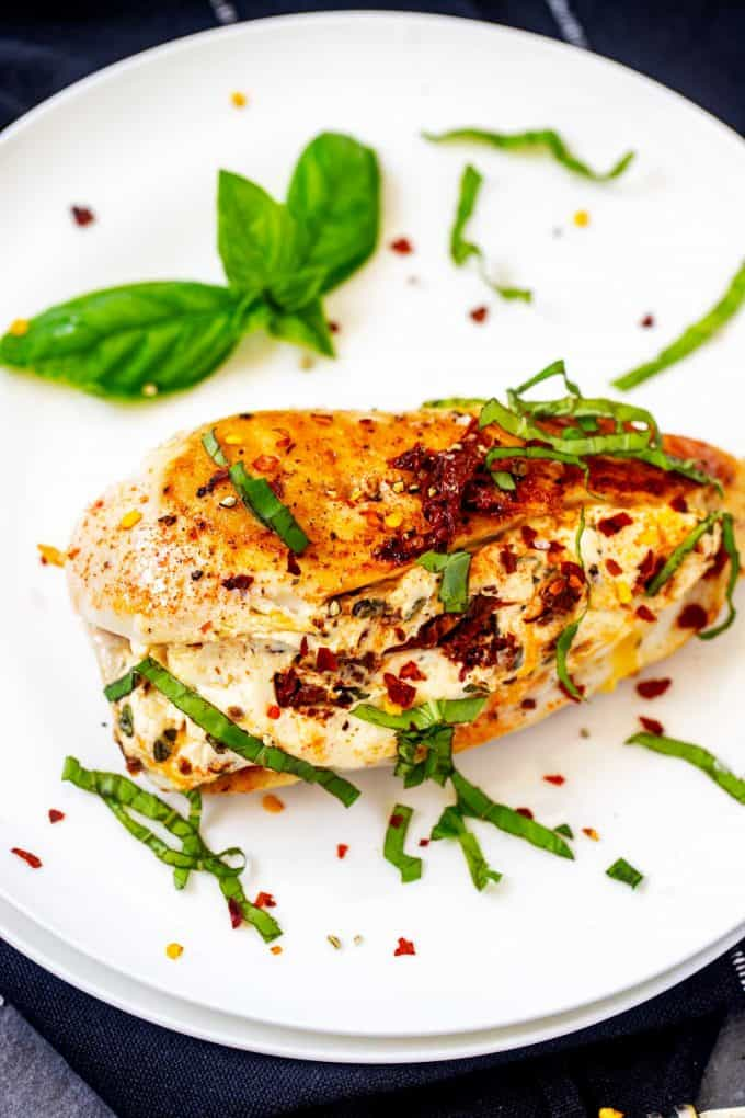 Photo of Keto Cream Cheese Chicken on a white plate garnished with basil.