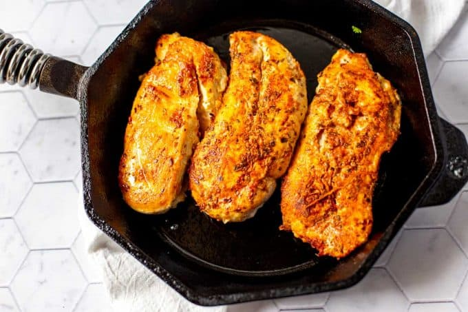 Photo a cast iron skillet with three chicken breasts being cooked.