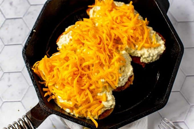 Photo of three chicken breast with a green chili cream cheese on top of them topped with shredded cheddar cheese.