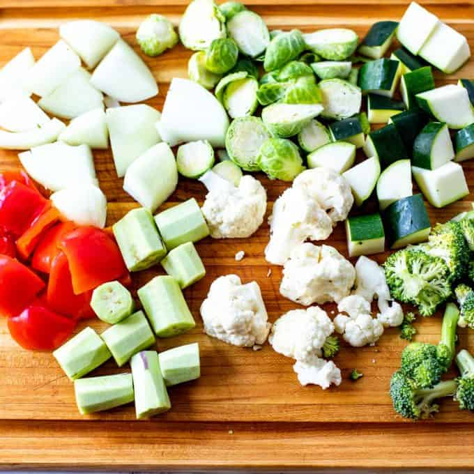 Cutting board with chopped onion, zucchini, brussels sprouts, red pepper, eggplant, cauliflower, and broccoli.