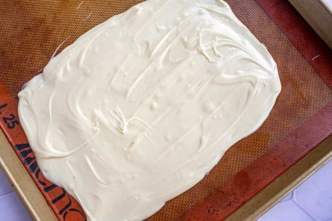 Keto white chocolate that has been melted and spread out on a lined baking sheet.