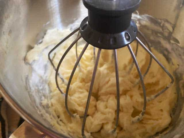 Photo of cream cheese frosting being whipped together in the bowl of a stand mixer.