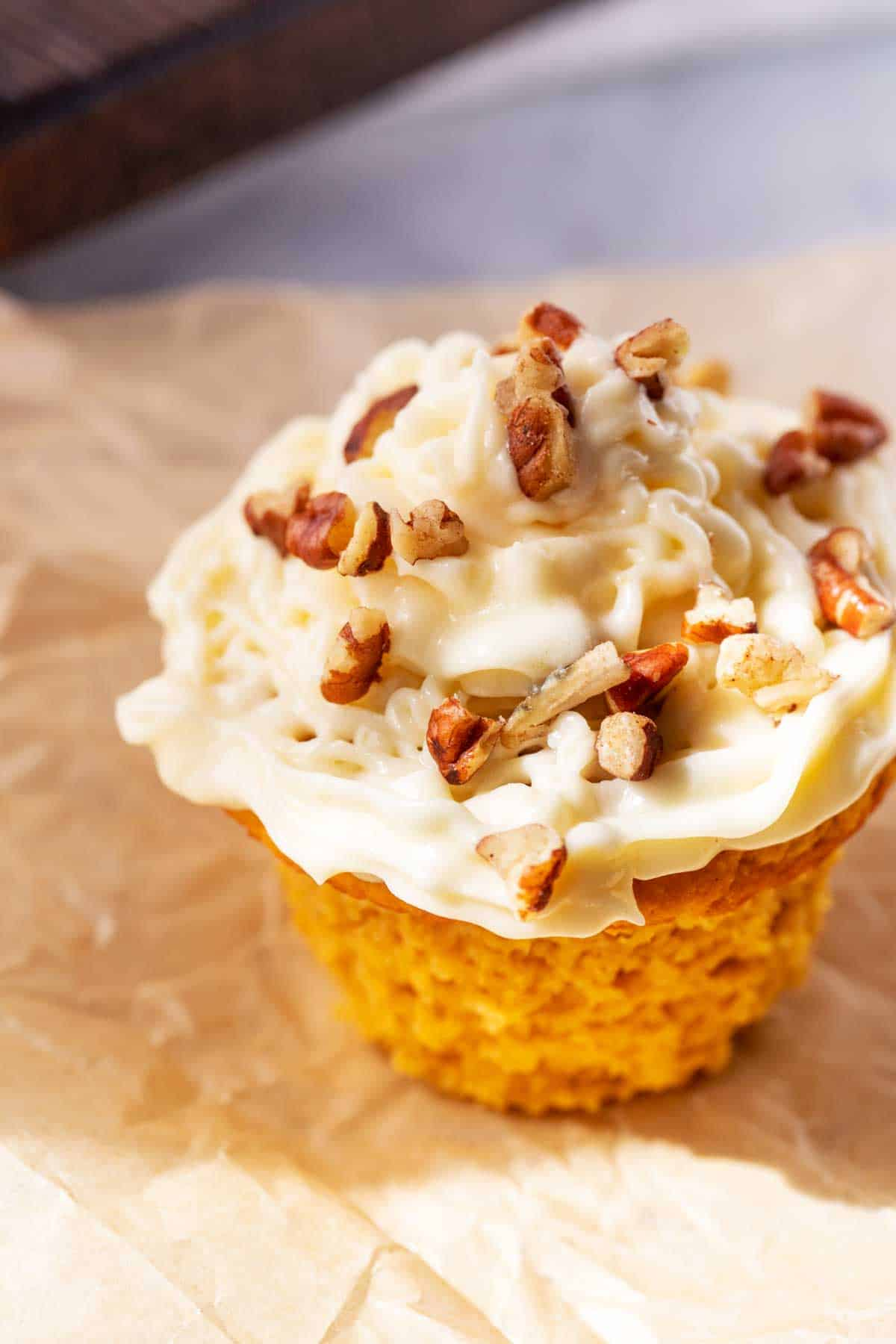 Close up photo of a Keto Pumpkin Muffin iced with cream cheese frosting and sprinkled with pecans.