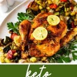 """¾ overhead photo of a whole roasted chicken on a platter on top of fresh herbs and roasted vegetables with the text. """"Great for meal prep - keto roasted chicken."""""""