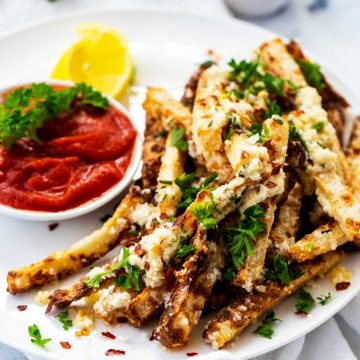 Square photo of a white place with Keto Jicama Fries with a small dish of ketchup on it.