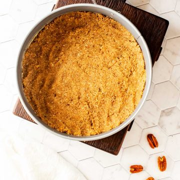 Square overhead photo of a Keto Pecan Crust in a springform pan sitting on a cutting board.