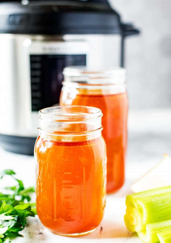 Photo of two jars of Instant Pot Chicken Bone Broth with an Instant Pot behind it.