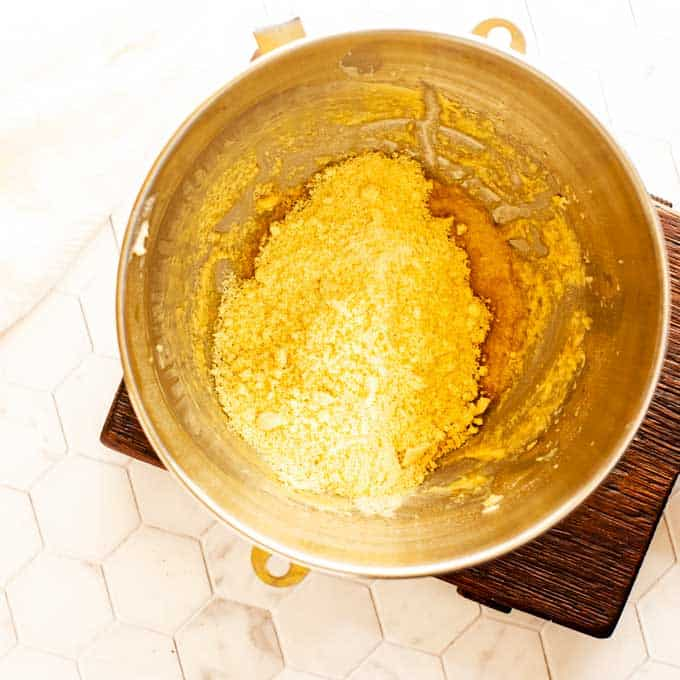 Photo of almond flour, oat fiber, baking powder, xanthan gum, and salt being added to a bowl of beaten egg and butter.