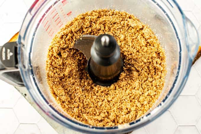 Photo of pecans, coconut, Swerve, and salt in a food processor.