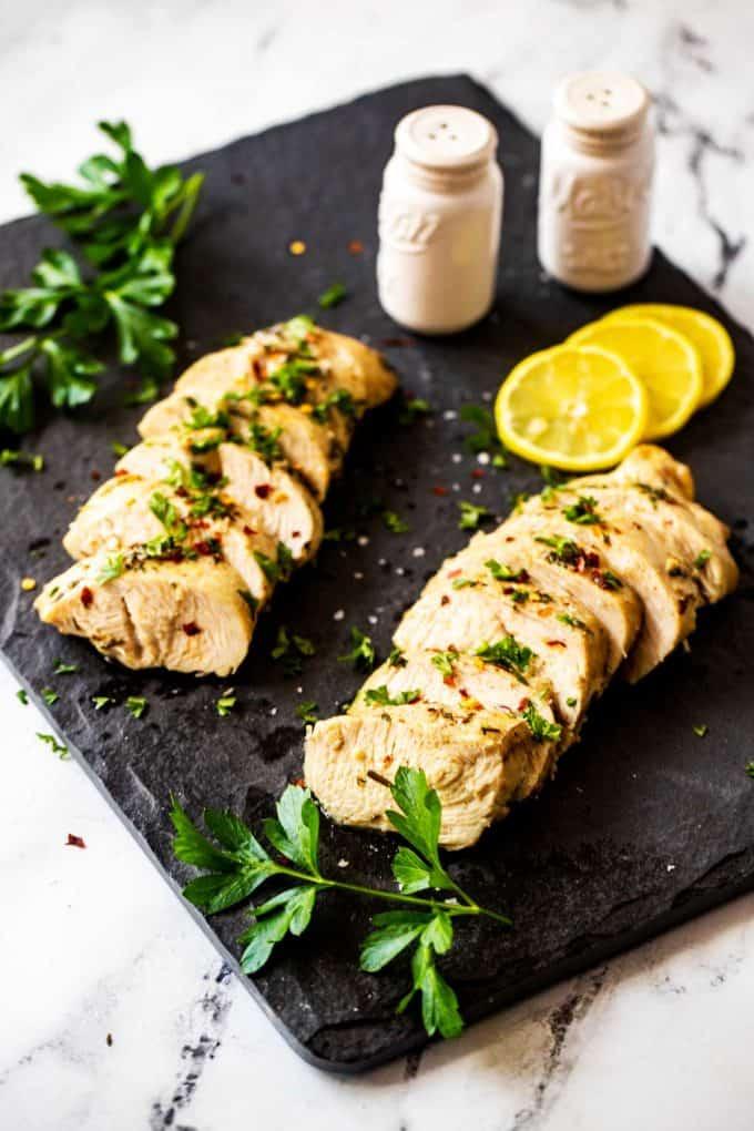Photo of sliced Keto Turkey Tenderloin on a dark slate board garnished with parsley.