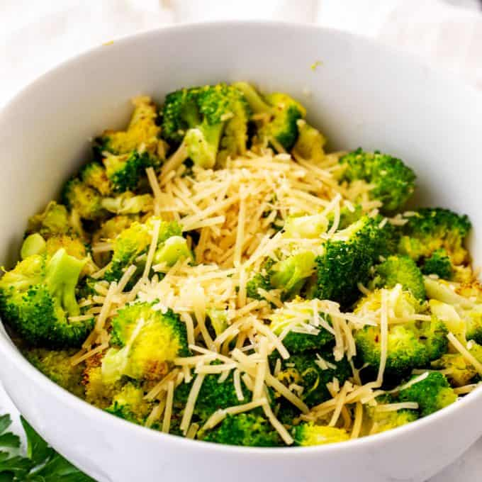 Bowl of crispy air fried broccoli topped with parmesan.