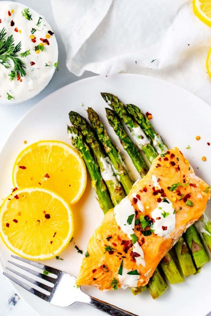 Plate of cooked Instant pot frozen salmon drizzled with lemon dill sauce on a white plate.