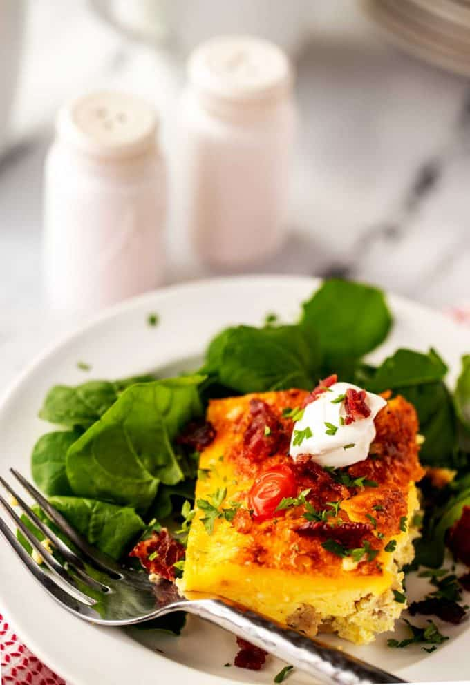 Square of keto egg casserole on a bed of greens.
