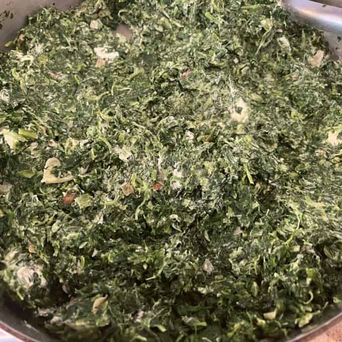 Photo of melted cream cheese incorporated into chopped spinach in a skillet.
