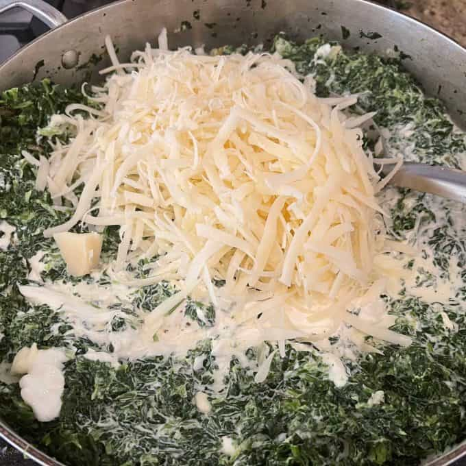 Photo of shredded cheese, heavy cream, and sour cream being added to a chopped spinach and cream cheese mixture.