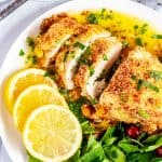 Square photo of buttery chicken kiev on a white plate garnished with parsley.
