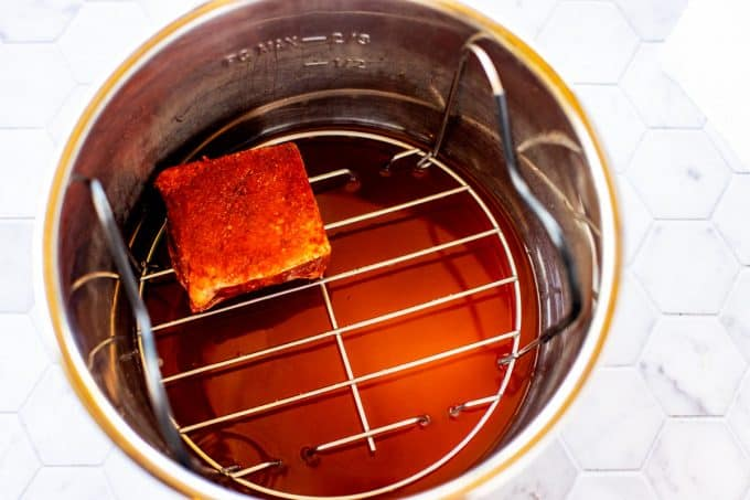 Photo of an Instant Pot with liquid in the bottom and a trivet with a short rib on it.
