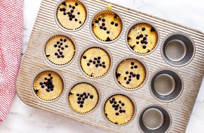 Photo of uncooked low carb blueberry muffins in a muffin tin ready for the oven.