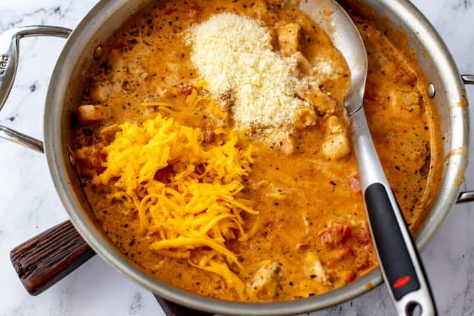 Photo of shredded cheddar cheese and parmesan cheese that have been added to a sauce for chicken spaghetti.