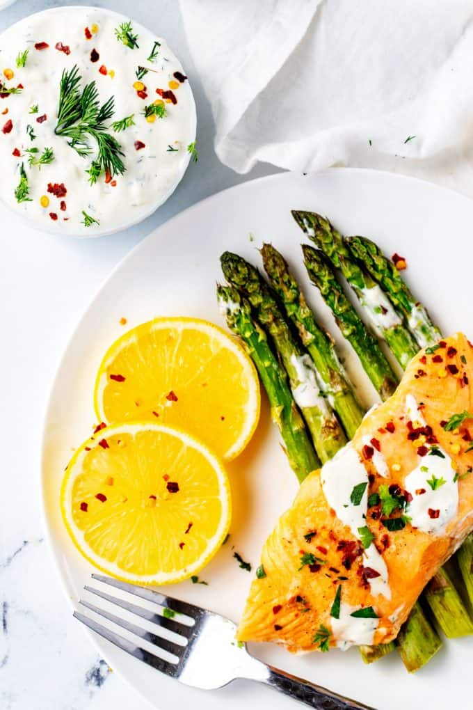 Photo of lemon dill sauce drizzled on salmon and asparagus with a small white bowl of sauce beside it.