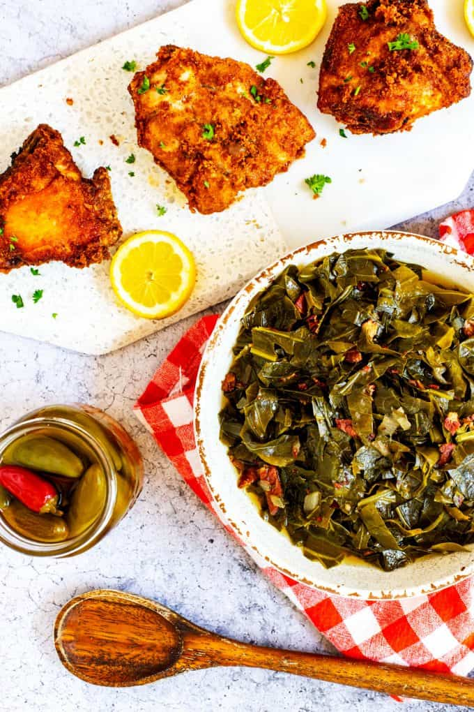 Southern Keto Collard Greens next to fried chicken and a jar of hot pepper sauce.