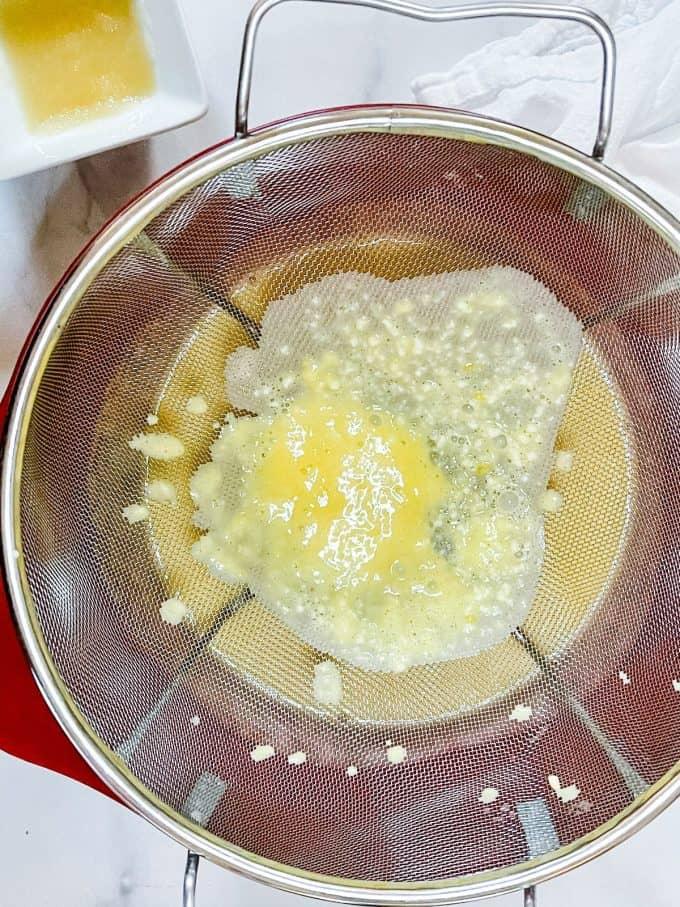 Photo of straining lemon curd.