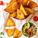 Square Overhead photo of a bowl of low carb tortilla chips with a few chips scattered below and a small bowl of guacamole.