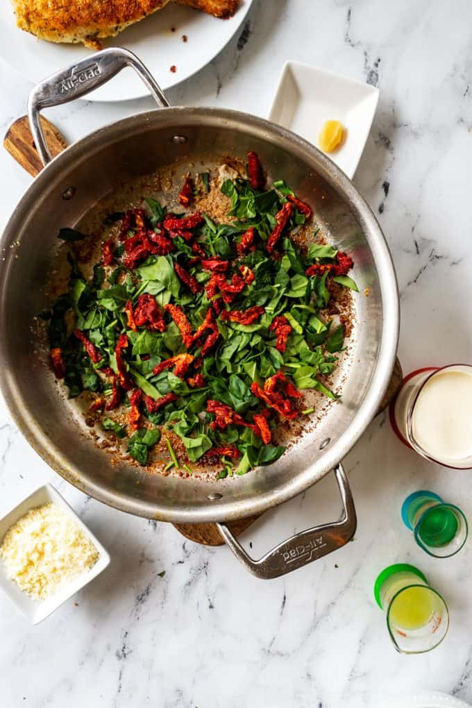 Photo of spinach and sun dried tomato in a skillet.