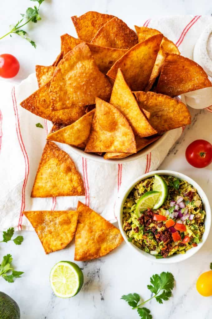 Overhead photo of a bowl of low carb tortilla chips with a few chips scattered below and a small bowl of guacamole.